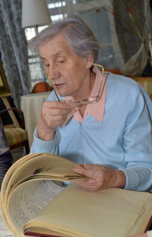 Janina Pawłowska przegląda przez siebie napisane kroniki miejskie