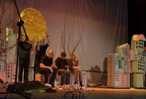 artyści na scenie, drzewo, słońce imitacje budynków z kartonu od lewej aktorzy niepełnosprawni na scenie