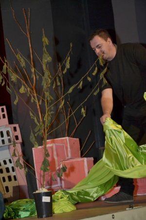 artysta stoi na scenie okrywa drzewo zielonym płaszczem