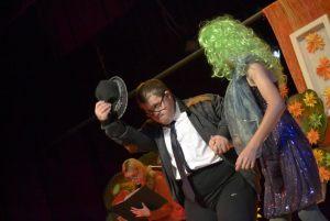 aktorzy prezentują scenkę: gruby mężczyzna w okularach zdejmuje kapelusz, rozmawia z partnerką która ma zielone włosy