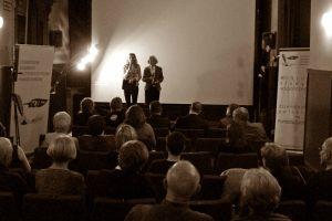 """Anna Kolmer i Helena Kwiatkowska zapraszają zgromadzoną publiczność do obejrzenia filmu """"Wielka Zielona Ściana - Afryka Afryce"""" zgromadzoną publiczność"""