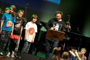 Z lewej strony dzieci na scenie i Mietek Szcześniak
