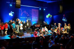 Mietek Szcześniak, na scenie dzieci oraz zespół muzyków towarzyszących