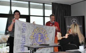Prezydent Ewa Kołodziejek i gubernator Okręgu 121 Polska Radosław Bilicki prezentują flagę z podpisami wszystkich polskich Lionów