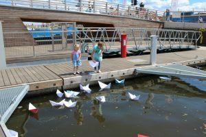 dzieci bawią się zwodowanymi papierowymi stateczkami z poezją