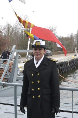 Kpt. Marynarki Wojennej Katarzyna Mazurek stoi na tle biało czerwonej bandery