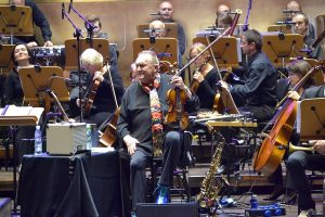 Michał Urbaniak w trakcie koncertu słucha orkiestry
