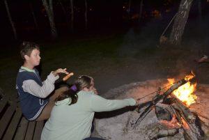 kolejni uczestnicy spotkania przy ognisku pieką kiełbaski